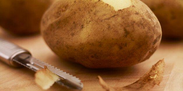 Close up of potato and peeler on cutting