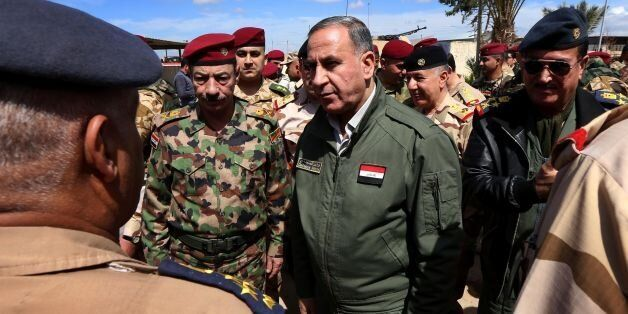 Iraqi Defence Minister Khaled Al-Obeidi (C) meets soldiers holding a position on the frontline during...
