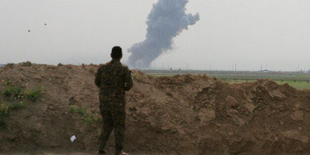 Smoke rises from positions in the Islamic State group held town of Besher, during a military operation...