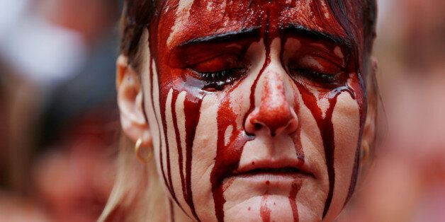 An animal rights protester covered in fake blood reacts during a demonstration for the abolition of bull...