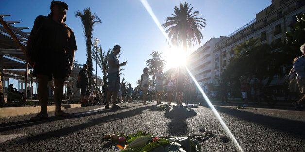 People lay flowers at the site of a deadly truck attack on the famed Promenade des Anglais in Nice, southern...