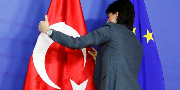 A staff adjusts European Union and Turkish (L) flags ahead of the arrival of Turkey's Prime Minister...