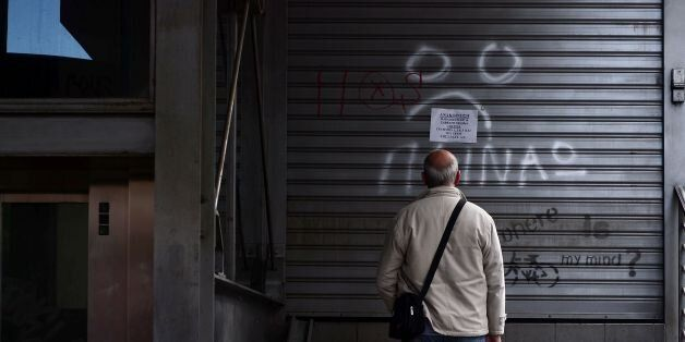A man reads an announcement while a writing reads 'I m hungry' at a closed urban railway station in Athens,...