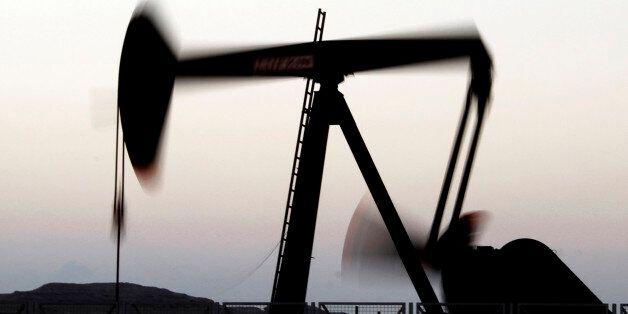 An oil pump works at sunset in the desert oil fields of Sakhir, Bahrain, Tuesday, Nov. 27, 2012. The...