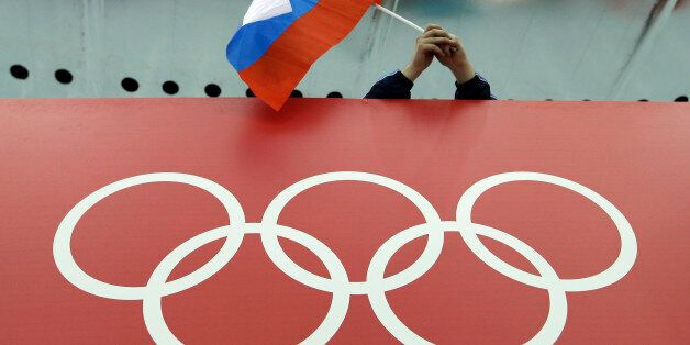 FILE - In this Feb. 18, 2014, file photo, a Russian skating fan holds the country's national flag over...