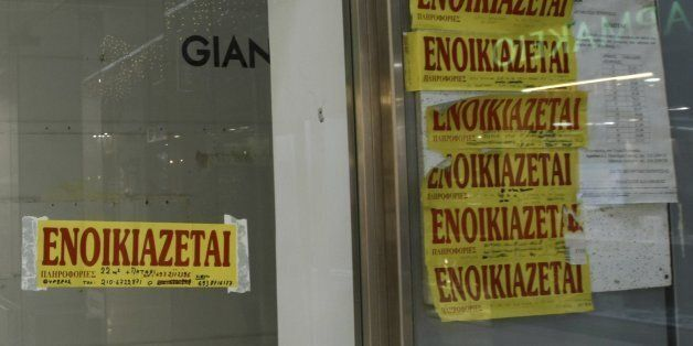 People walk outside empty stores with rental signs posted on glass windows in central Athens December...