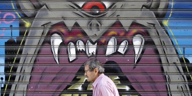 A man walks past graffiti painted on a closed shop at Monastiraki area in central Athens, Greece, July...