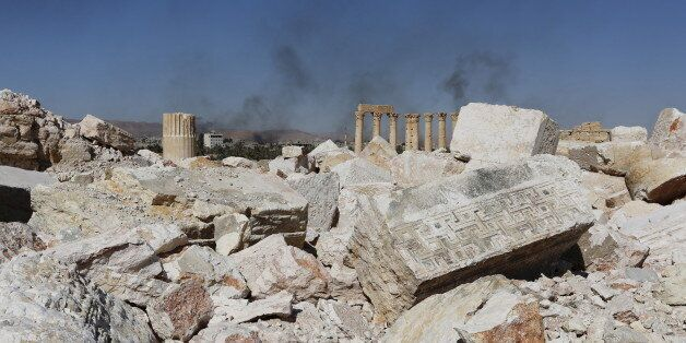 Smoke rises from the modern city as seen from the historic city of Palmyra, in Homs Governorate, Syria...