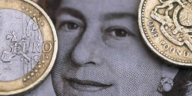 A two Euro coin is pictured next to a one Pound coin on top of a portrait of Britain's Queen Elizabeth...