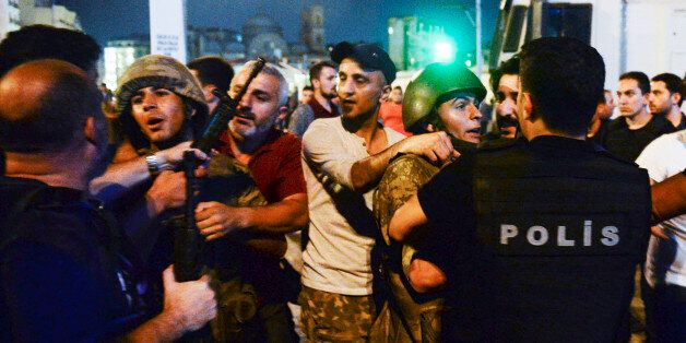Turkish soldiers, arrested by civilians, are handed to police officers, in Istanbul's Taksim square,...
