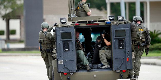 FBI patrol the perimeter of the crime scene in an armored vehicle where Baton Rouge police were shot,...