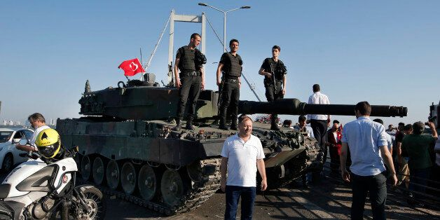 People gather around as Turkish police officers, loyal to the government, stand atop tanks abandoned...