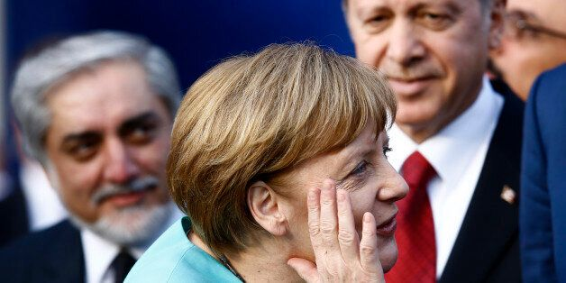 German Chancellor Angela Merkel (C) reacts next to Afghanistan's Chief Executive Abdullah Abdullah (L)...
