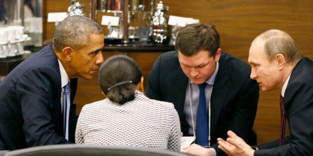 U.S. President Barack Obama (L) talks with Russian President Vladimir Putin (R) and U.S. security advisor...