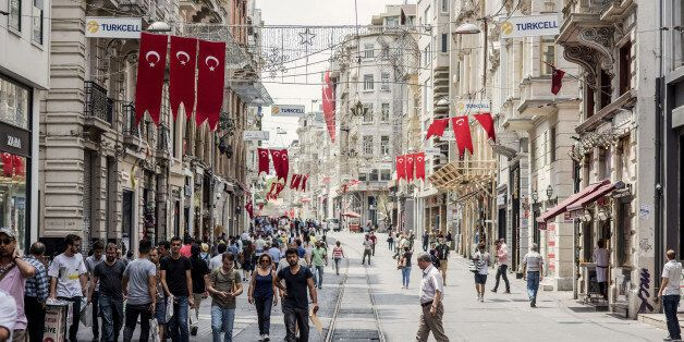 Banners of the Turkish national flag hang above pedestrians passing along a half empty Taksim street...