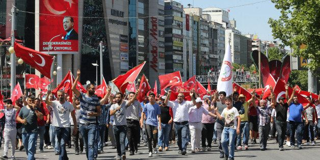 People wave national flags as they march from Kizilay square to Turkish General Staff building to react...