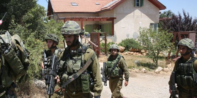 Israeli soldiers stand guard outside a house in the Jewish settlement of Kiryat Arba in the occupied...