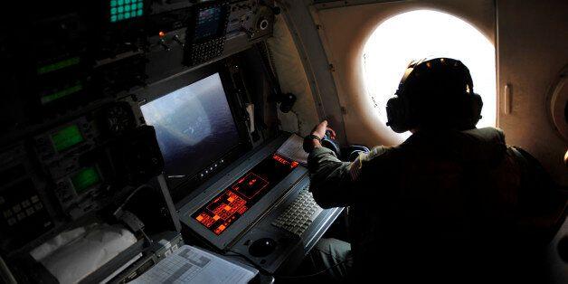 U.S. Navy LT. JG Dylon Porlas looks out the window of a U.S. Navy Lockheed P-3C Orion patrol aircraft...