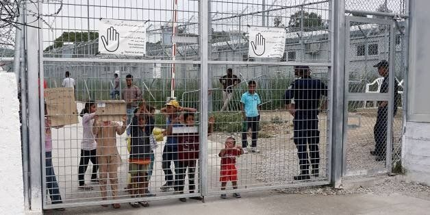 Children hold plackards at the Moria detention camp for migrants and refugees at the island of Lesbos...