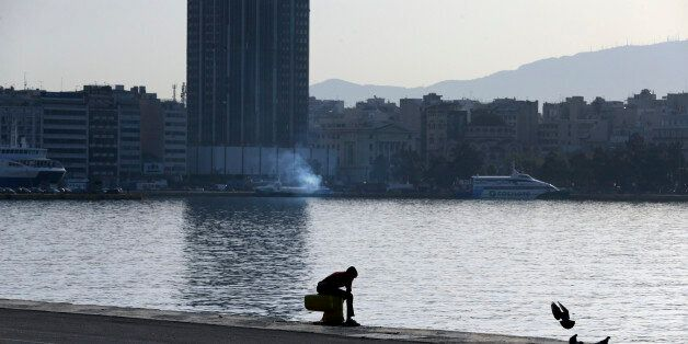 A migrant sits at the Athens port of Piraeus, Monday April 4, 2016, during the first day of the implementation...