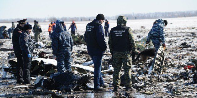 Russian Investigative Committee employees, center, and police officers investigate the wreckage of a...