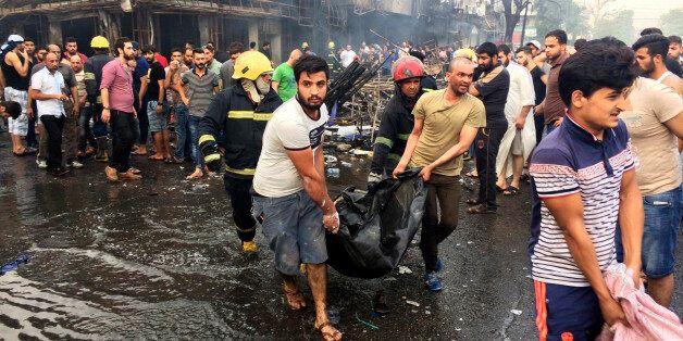 Iraqi firefighters and civilians carry bodies of victims killed in a car bomb at a commercial area in...
