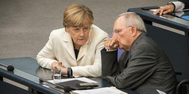 German Finance Minister Wolfgang Schaeuble (R) and German chancellor Angela Merkel attend a parliament...