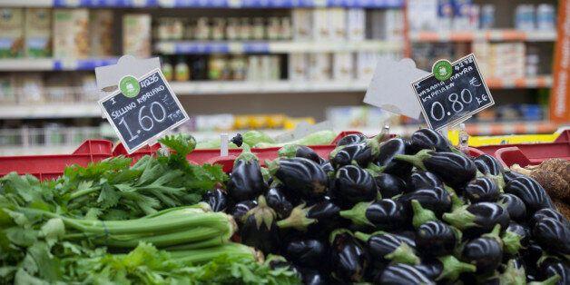 Euro price signs sit on vegetables, including celery, left, and aubergines, right, for sale inside a...