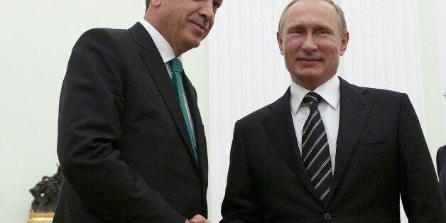 Russian President Vladimir Putin (R) shakes hands with Turkish President Tayyip Erdogan during their...