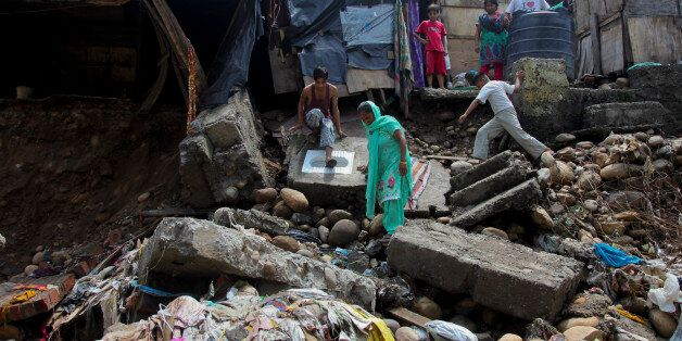 Indian residents look at the remains of their house damaged in flash floods on the outskirts of Jammu,...