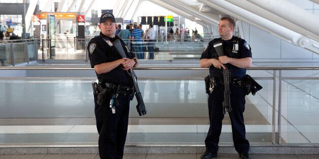 NEW YORK, NY - JUNE 30: Port Authority police officers stand guard near a departures entrance at John...