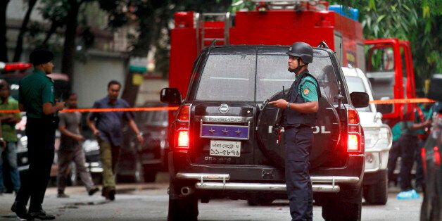 Bangladeshi security officers cordon off an area after heavily armed militants attacked a restaurant...