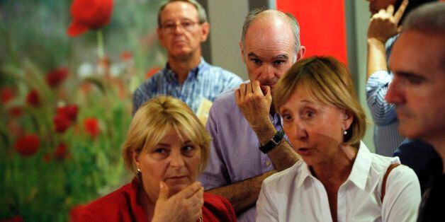 People wait for election results at Spain's Socialist Party (PSOE) headquarters after polling stations...