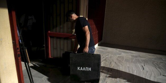 A man carries a ballot box at a voting centre in Athens, Greece, September 18, 2015. An election campaign...