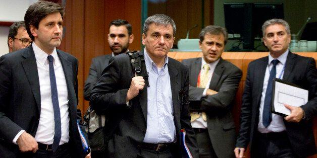 Greece's Finance Minister Euclid Tsakalotos, center, arrives for a meeting of eurogroup finance ministers...