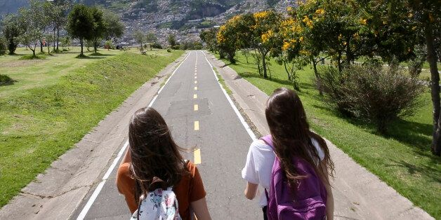 Two students walk down paved trail in park