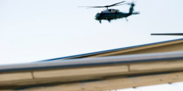 Marine One, bottom, with President Barack Obama aboard, flies behind the wing of Air Force One, at Andrews...