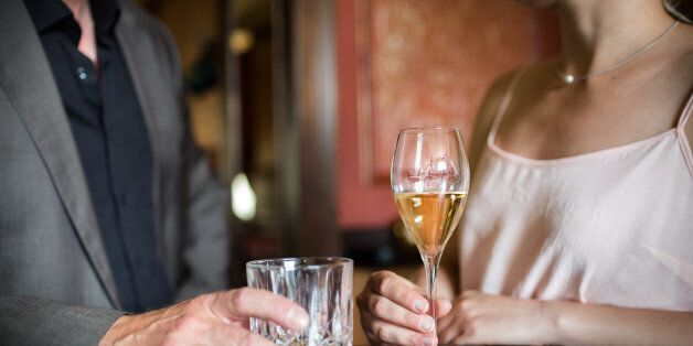 Man and woman flirting at a bar while holding drinks. Close-up shot of their