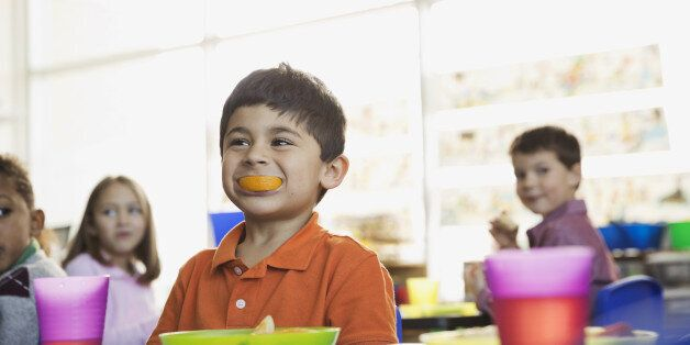 Playful boy holding orange slice in mouth at school at snack