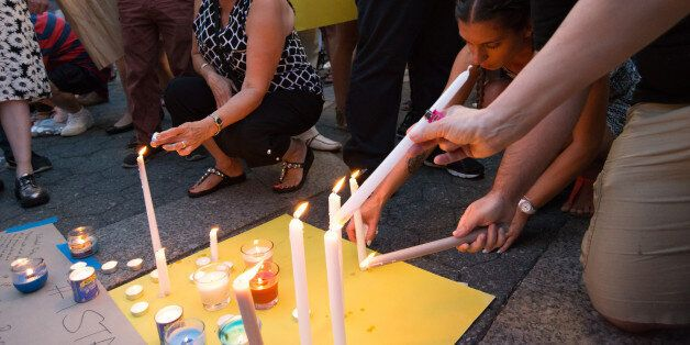 UNION SQUARE PARK, NEW YORK, NY, UNITED STATES - 2016/06/29: Vigil participants light candles and write...