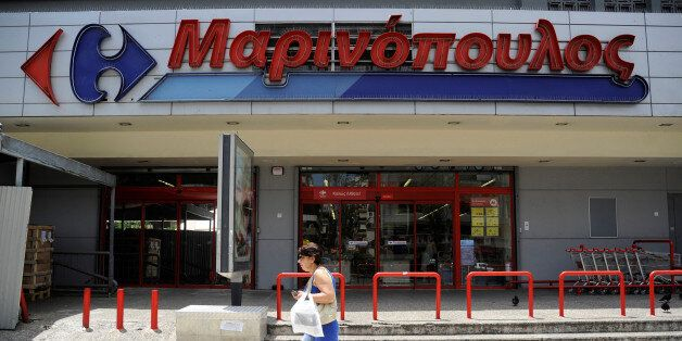 A woman walks past a Marinopoulos supermarket, while the Greek retail group Marinopoulos applies for...