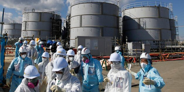 FILE - In this Feb. 10, 2016, file photo, members of a media tour group wearing a protective suit and...