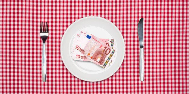 Ten Euro notes on a white dinner plate with knife and fork on a red checked tablecloth. Cost of food...