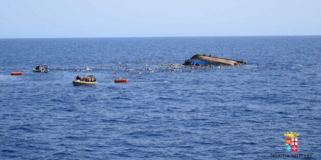 People swim next to an overturned boat off the Libyan coast, Wednesday, May 25, 2016. The Italian navy...