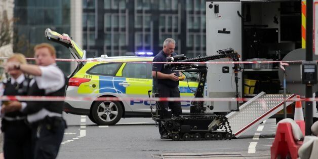 Police prepare to send a robot to investigate an abandoned car on Westminster Bridge, close to the Palace...