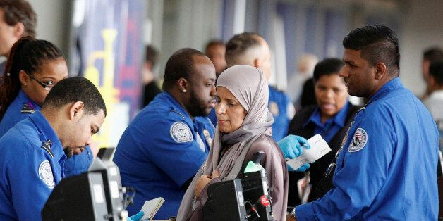 Transportation Security Administration (TSA) agents check-in passengers at JFK airport in the Queens...
