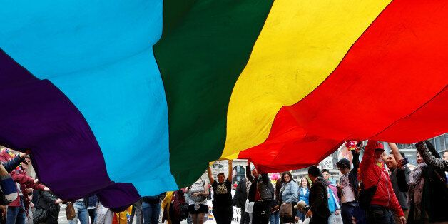 Participants hold a giant rainbow flag during the Belgian LGBT Pride Parade in central Brussels, Belgium,...