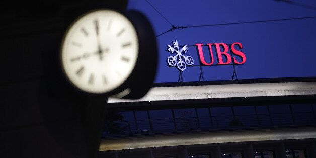 A sign sits illuminated on the roof of the UBS Group AG headquarters in Zurich, Switzerland, on Monday,...
