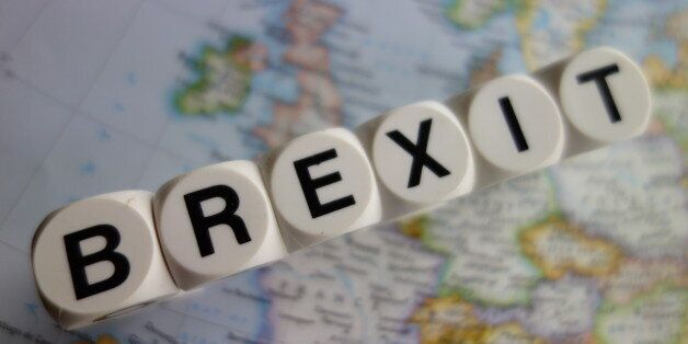 Word brexit in black lettering on white cubes, with the united kingdom on one side and Europe on the