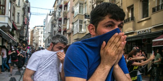 People cover their face with t-shirts as Turkish anti-riot police officers fire rubber bullets to disperse...